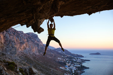 Male rock climber gripping handhold on ceiling in cave