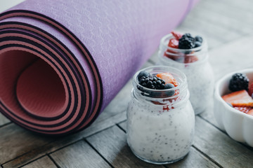 Sport and healthy concept. Pink yoga mat and Pudding with chia seeds, yogurt and fresh fruits: Strawberries, blueberries and blackberries in glass jars on wooden background