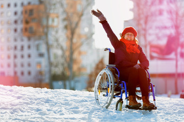 adult woman on wheelchair waving