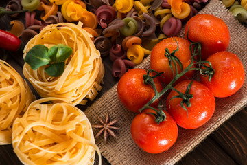 A branch of tomatoes against the background of pasta and spices. Ingredients for Italian dishes. Close-up
