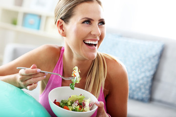 Young woman eating healthy salad after workout Wall mural