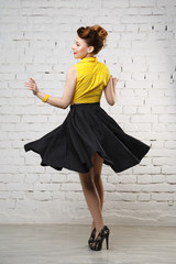 Beautiful cheerful dancing girl in the style of pin-up in half a turn in full growth.