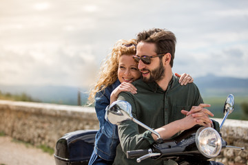 Young couple on motorbike together looking at view