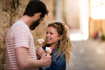 Young female eating gelato with boyfriend