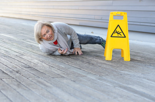 Senior lady slipping and falling on a wet surface