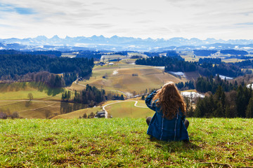 Girl standing behind me watching the mountain landscape