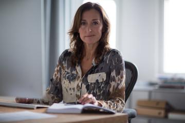 Portrait of mature businesswoman at desk
