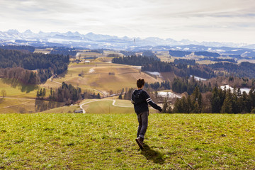 Boy throws stick, mountain landscape, the concept of anger