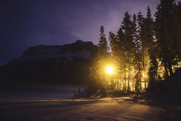 Illuminated snow covered landscape, mountains and starry sky