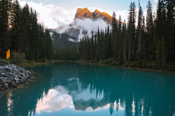 Reflection of trees and mountain peaks on turquoise lake