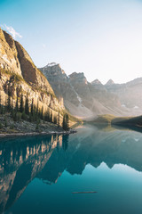 Reflection of mountain peaks and sky on turquoise river