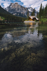 Cabin by riverside, snow capped mountains and woodland