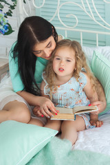 Pretty young mother having fun with her little daughter in bedroom. Beautiful mom and her child spending time together indoors. Mom reading a fairytale to her daughter.