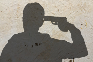 shadow of a man with pistol gun turned on his head wants to commit suicide