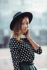 Beautiful young woman in a hat stands on the street