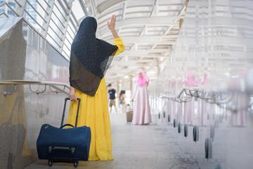 Arab traveler woman walking carrying a suitcase