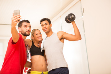 Group of young sporty people make a selfie with smartphone in gym
