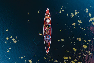 Canoeist and leaves floating on water surface, aerial view