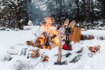Campfire burning in snow covered landscape,