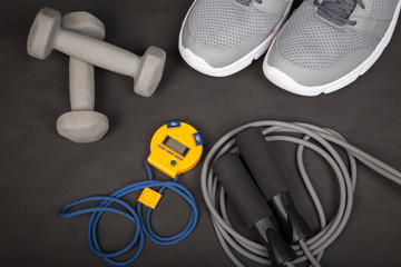 Sport shoes, dumbbells, skipping rope and digital stopwatch. Top view. Fitness, sport and healthy lifestyle concept.