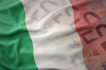colorful waving national flag of italy on a euro money banknotes background. finance concept