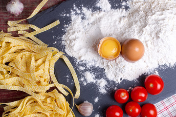 Fettuccine paste, egg, flour, garlic, cherry tomato and rosemary on a chopping board