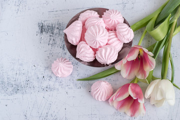 Gentle dessert. Three blooming tulips and a vase with gentle meringues on a light background.