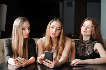 always connected, internet addiction, young girls in cafe looking at their smartphones, social network concept