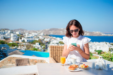 Young woman with smartphone in outdoor cafe. Happy girl enjoy morning time in cafe with beautiful view