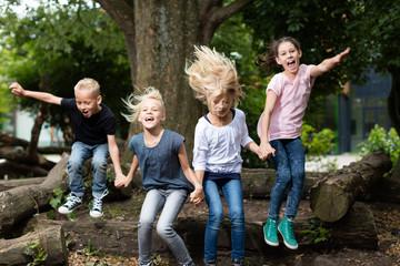 Kinder springen auf dem Schulhof