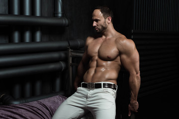 Sexy young shirtless handsome bodybuilder sits on a bed in a room with unusual design with pipes on the wall