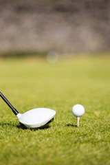 Close up view of a golf club driver on a golf course with a golf ball ready to be driven down the fairway