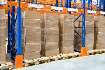 Boxes with goods in a large distribution warehouse with metal racking storage system