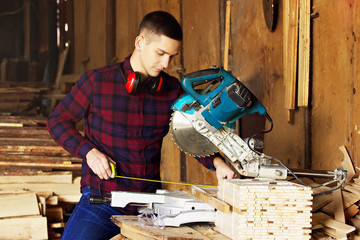 Workman dressed in the checkered shirt working with tape-measure near circular saw. Timbers on background.