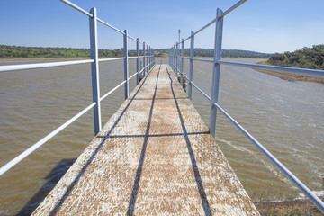 Modern footbridge attached to Dam of Cornalvo Reservoir, Extremadura, Spain