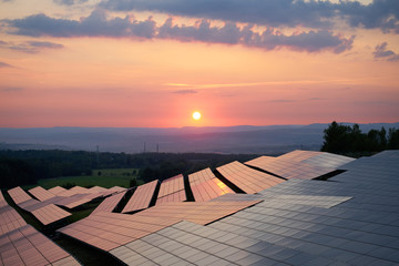 Sunset over solar power station in countryside. View from above.