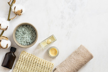 Spa beauty cosmetic products and tools on white marble background. Top view, copy space
