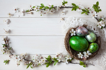 Easter background with a nest, eggs and branch with flowers