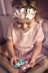 Beautiful little girl in pink dress playing in toys