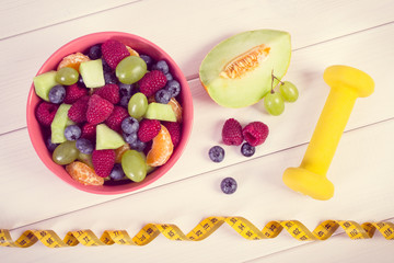 Vintage photo, Fresh fruit salad and centimeter with dumbbells, healthy lifestyle and nutrition concept