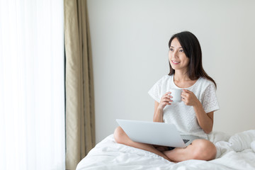 Woman working on notebook computer and enjoy her coffee