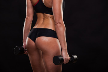 Booty of attractive athletic woman holding dumbbells, back view isolated on dark background with copyspace