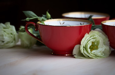 Red teacup on a wooden table surrounded by beautiful green flowers