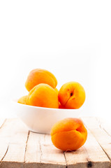 Few fresh peaches in white cup on wooden table