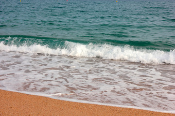 Strip of coastal sandy beach and calm waves of the Mediterranean Sea