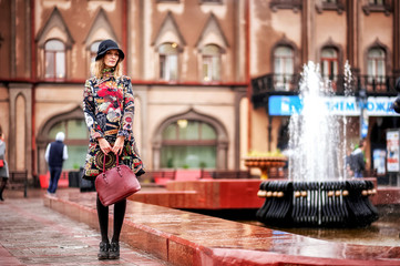A beautiful girl in a bright multi-colored coat in rainy weather against a bright brick old castle or a house. Fountain in the background. Saratov, Russia.