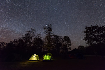 Camping tent glows under a night sky full of stars.