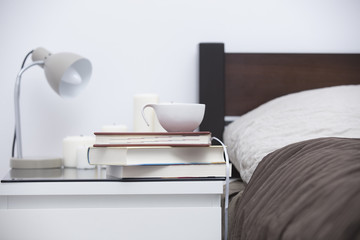 pile of books, notebook, cup of coffee, candles and lamp on the table near bed in the bedroom