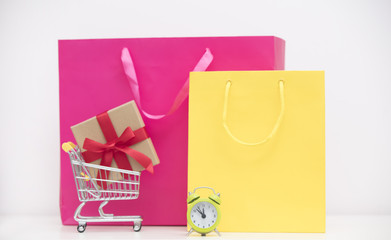 cool shopping bags, gift in shopping cart and alarm clock on the wonderful white background