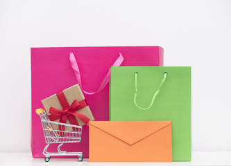cool shopping bags, gift in shopping cart and envelope on the wonderful white background
